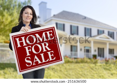 Smiling Hispanic Female Holding Sold For Sale Sign In Front of Beautiful House. - stock photo