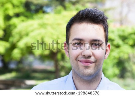 Smiling hispanic guy in a blue shirt outside in a park - stock photo