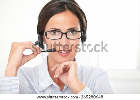 Smiling hispanic secretary with spectacles talking on headphones and looking at you, taken as headshot - stock photo