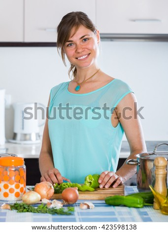 smiling housewife cooking vegetables basing on new recipe indoors