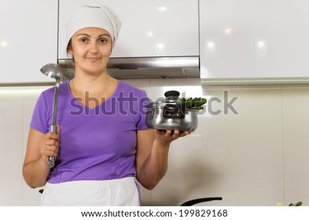 Smiling housewife standing showing pot before she cooks it - stock photo