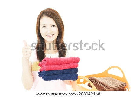 Smiling housewife with a laundry basket - stock photo