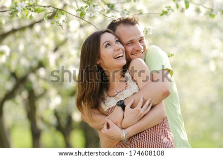 smiling hugging couple in bloomy garden - stock photo