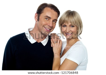 Smiling husband and wife striking a romantic pose. Indoor studio shot. - stock photo