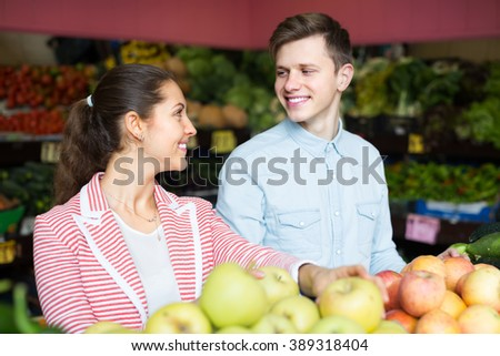Smiling husband helping young brunette to choose veggies and fruits