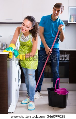 Smiling husband helping young housewife doing regular clean up at kitchen