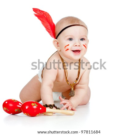 smiling Indian boy baby with feather playing with maracas - stock photo