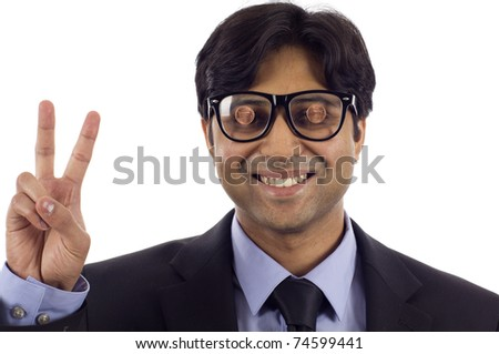 Smiling Indian business man wearing a black glasses with 2 cents on it, he's making a victory sign isolated over white  background