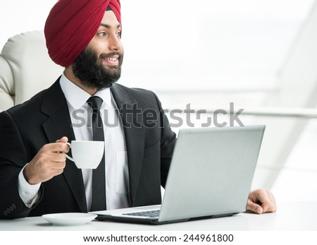 Smiling indian businessman is working on his computer in the office. - stock photo