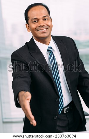 Smiling Indian businessman outstretching hand for a handshake - stock photo
