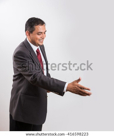 Smiling Indian businessman outstretching hand for a handshake, asian businessman offering hand shake or shake hand or shakehand