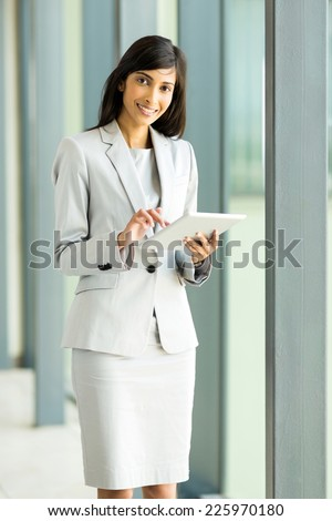 smiling indian businesswoman with tablet computer in office - stock photo
