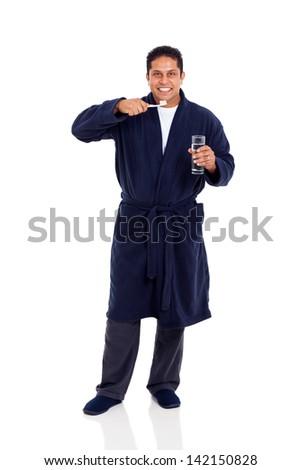 smiling indian man wearing pajamas brushing teeth isolated on white background - stock photo