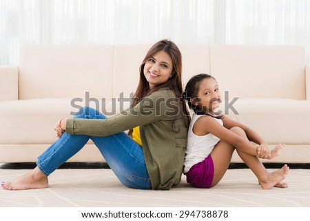 Smiling Indian mother and daughter sitting on the floor back to back - stock photo
