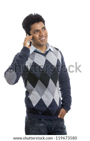 smiling Indian young man talking on the mobile phone  white background. - stock photo
