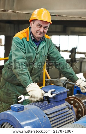 smiling industrial worker with spanner at factory workshop