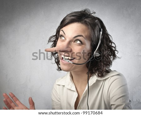 Smiling insincere receptionist with long nose talking on the telephone - stock photo