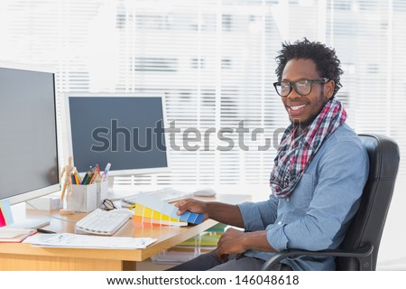 Smiling interior designer holding colour charts in a modern office - stock photo