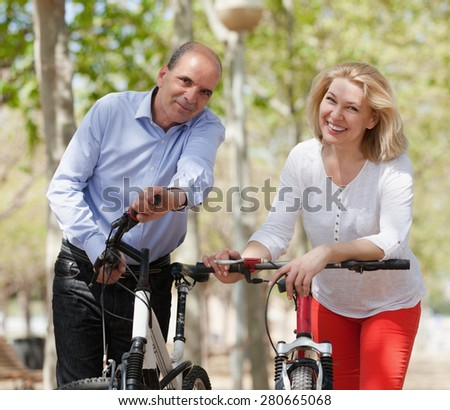 Smiling international family of active pensioners with bikes outdoor in sunny day