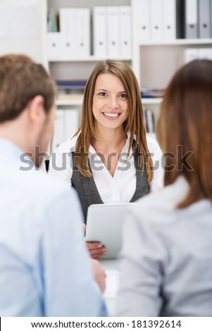 Smiling investment broker talking to clients as they sit together at a desk in her office, view between the young couples shoulders from behind - stock photo