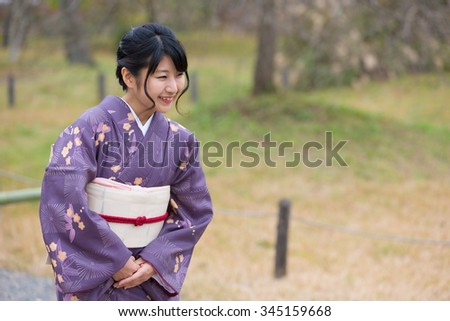 Smiling Japanese girl in a purple seasonal kimono bowing - stock photo