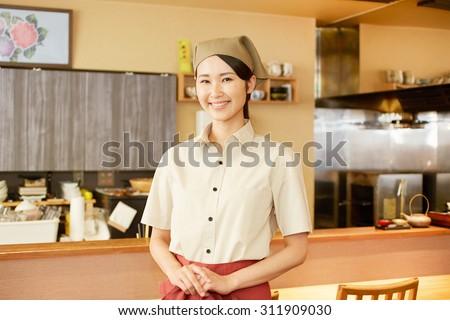 smiling Japanese restaurant clerk - stock photo