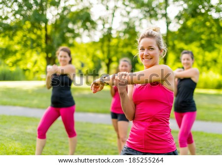 Smiling jogging coach stretching in th park - stock photo