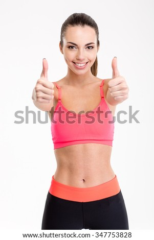 Smiling joyful fitness girl in sportwear showing thumbs up with both hands over white background - stock photo