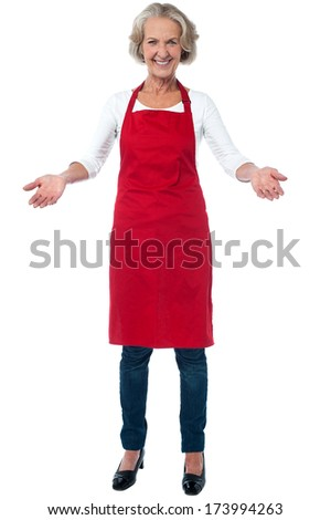 Smiling joyous aged female chef with open arms