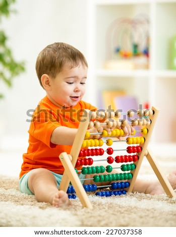 smiling kid boy playing with counter toy