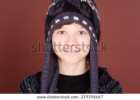 Smiling kid boy posing in knitted winter hat over beige