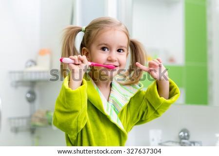 Smiling kid child girl brushing teeth in bathroom - stock photo