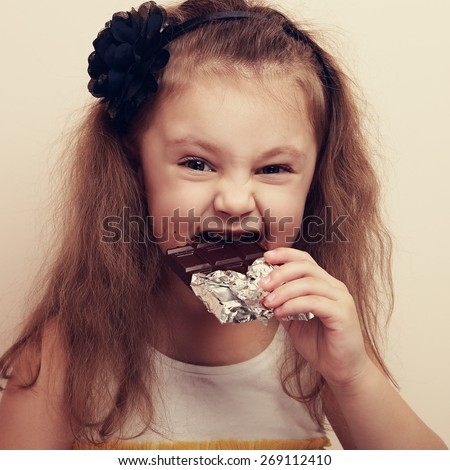 Smiling kid girl biting dark chocolate with craving fun eyes. Vintage closeup portrait - stock photo