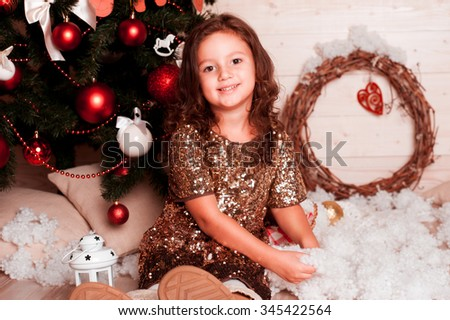 Smiling kid girl playing with decorative snow under Christmas tree in room. Looking at camera. Enjoyment. - stock photo
