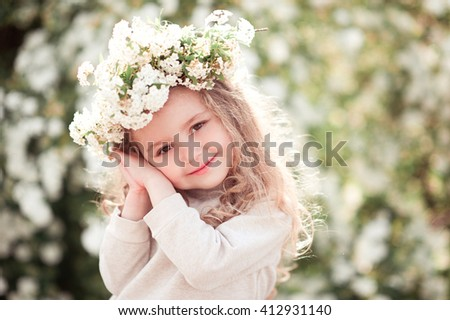 Smiling kid girl posing with flower wreath outdoors. Looking at camera. Childhood. - stock photo