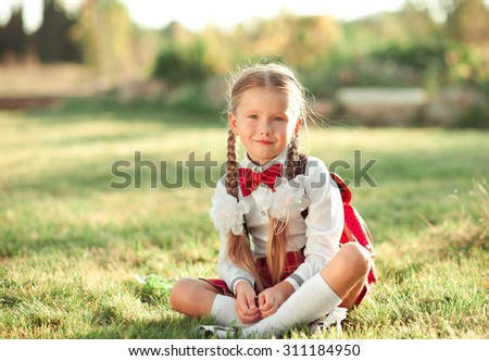 Smiling kid girl wearing school uniform outdoors. Sitting on grass in meadow. Looking at camera. Childhood. Back to school.  - stock photo