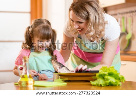 smiling kid girl with mom cooking fish in domestic kitchen - stock photo