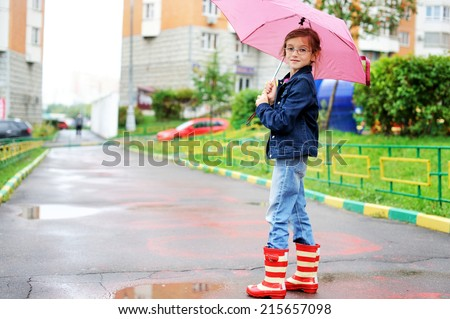 Smiling kid girl with umbrella in rain boots outdoor  in the city - stock photo
