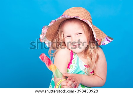 Smiling kid girl 5-6 year old eating ice cream in room over blue. Looking at camera. Wearing stylish swimsuit and hat in room. - stock photo