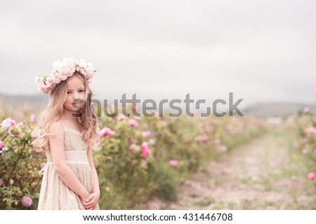 Smiling kid girl 4-5 year old posing in rose garden wearing stylish dress and flower hairband outdoors. Looking at camera. Childhood.  - stock photo