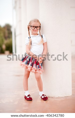 Smiling kid girl 5-6 year old wearing backpack outdoors. Looking at camera. Childhood. - stock photo