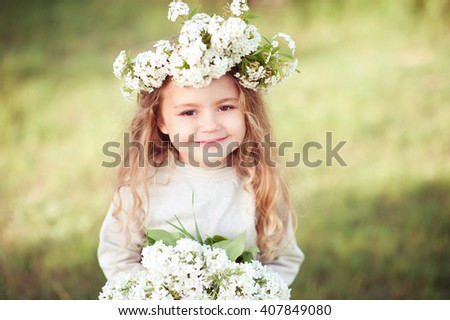 Smiling kid girl 4-5 year old wearing flower wreath, holding bouquet of lilac outdoors. Looking at camera. Summer time.  - stock photo