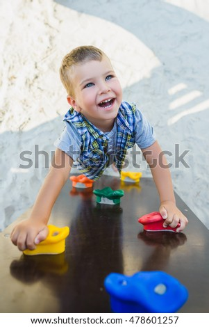 Smiling kid having fun at playground. Child doing gymnastic exercises