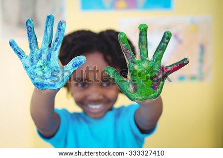 Smiling kid holding up his hands covered in paint - stock photo