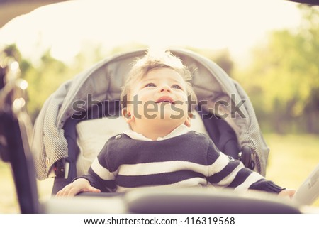 Smiling kid in pram looking up in warm sunny day - stock photo