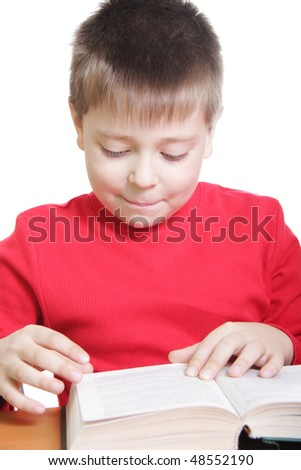 Smiling kid in red reading book at desk against white background