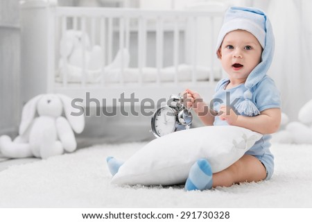 Smiling kid in the nightcap with an alarm clock and a pillow on the carpet in my room - stock photo