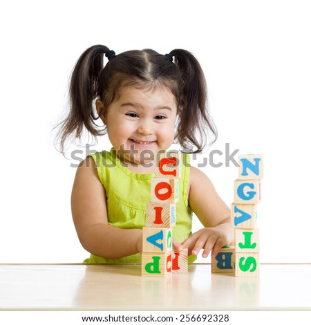 smiling kid little girl is building a toy block sitting at table - stock photo