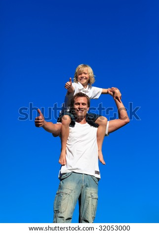 Smiling kid on his man's shoulders with thumbs up - stock photo