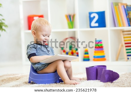 smiling kid sitting on chamber pot playing tablet pc - stock photo